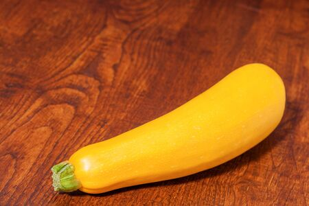 courgette: Fresh yellow courgette zucchini on wooden background. Stock Photo