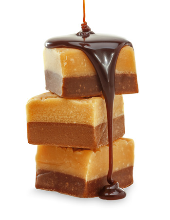 Chocolate flow on Fudge. Isolated on a white. Stock Photo