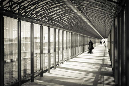 Indoor glass tunnel for pedestrians. Monochrome - black and white photography.
