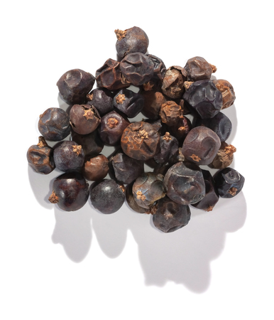 Dried juniper berries isolated on white. Soft focus view. Close up.
