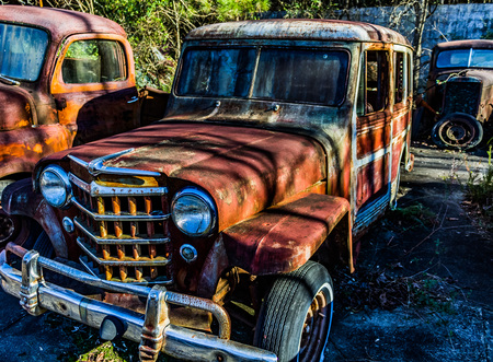rusty car: Rusty, old, junked car in the woods