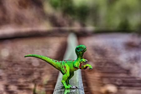 Green Velociraptor dinosaur  walking on  rail railroad tracks Archivio Fotografico