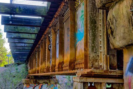 Old rustic rail road bridge over a small  river
