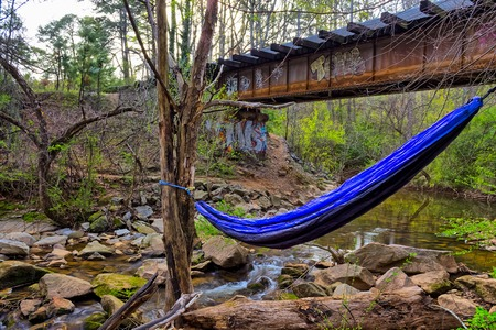 Old rustic rail road bridge with hammock and  river