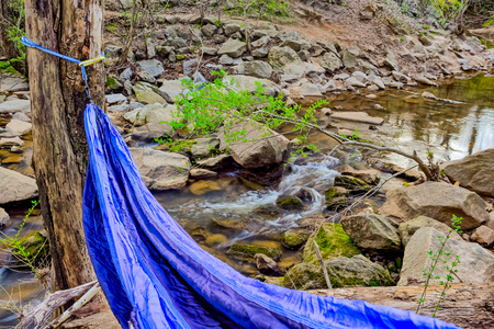 Blue hammock in the woods with a small  river