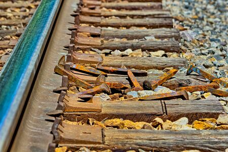 Rusty railroad spikes laying on ground in a  pile