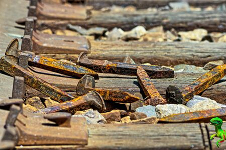railroad: Railroad spikes laying on ground in a pile with dino in the  corner Stock Photo