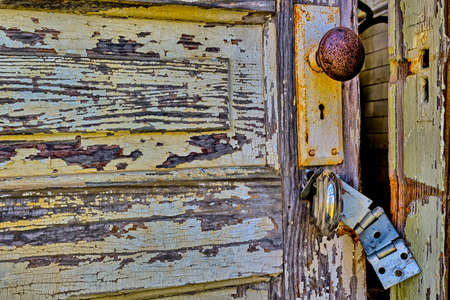 Old, rustic, partially open door with broken  latch