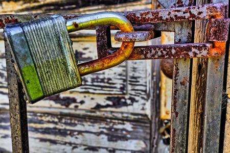 Rusty, old, locked padlock on a latch  horizontally