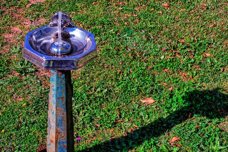 liquid reflect: Old, rustic, water fountain with a grassy  background