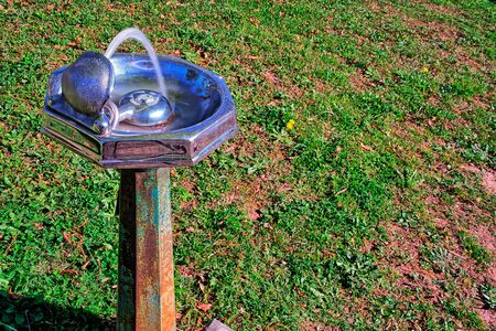Old, rustic, water fountain with a grassy  background