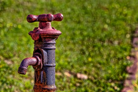 Old rusty looking faucet with grassy  background Stock Photo