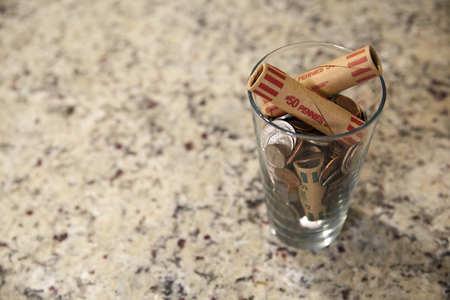 Glass jar of coins in cup on desk money savings debt bank rich poor dollar finance wealth change market cash