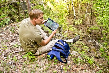 geo: he young man sits on the edge of a cliff and looks the GPS map Stock Photo