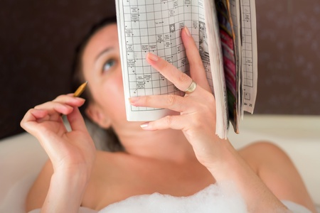 teaser: a woman in the bathroom at solving a crossword puzzle