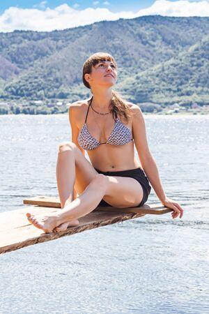 girl sunbathing on the river photo