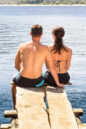 Vue d'un couple assis sur des chaises longues en profitant de vacances