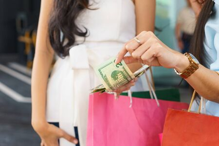 Woman is borrowing money from her friend for shopping.
