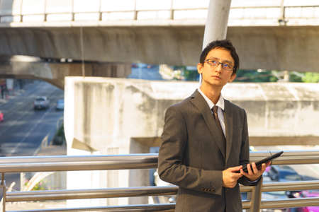 Middle aged Asian businessperson is holding tablet and thinking about his business.