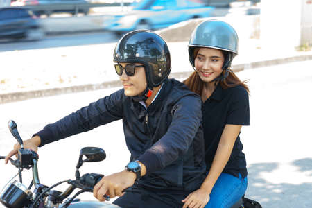 Middle aged Asian couple are riding motorcycle. Stock Photo