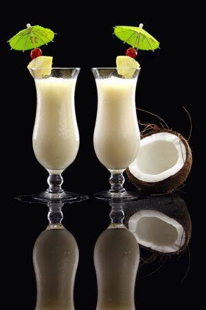 alcoholic drink: 2 Pi�a Colada & coco on black