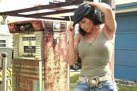 rusty car: Hitchhiker fitting her hat at a vintage gas pump Stock Photo