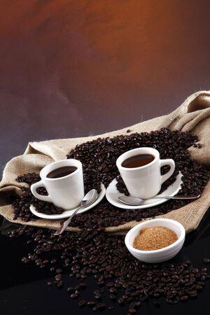 2 black coffee cups, grains, sisal sack and raw sugar