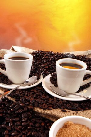 coffee cups: 2 black coffee cups, grains, sisal sack and raw sugar on yellow