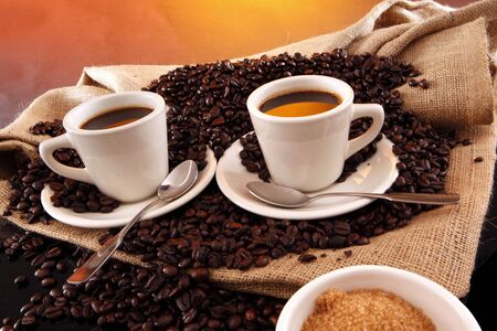 break: 2 black coffee cups, grains, sisal sack and raw sugar on yellow
