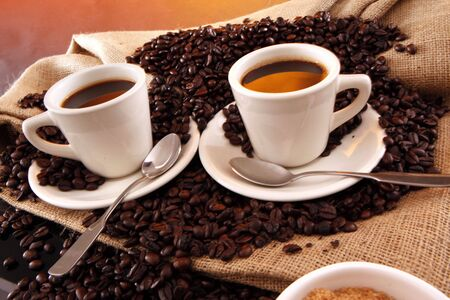 2 black coffee cups, grains, sisal sack and raw sugar on yellow
