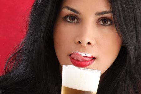 Cute brunette bier drinken en wens schuim uit haar lippen