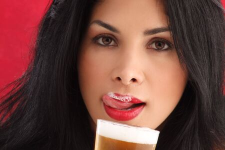 liking: Cute brunette drinking beer and liking foam from her lips Stock Photo
