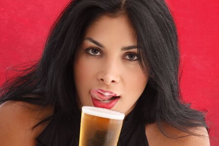 Cute brunette drinking beer and liking foam from her lips photo
