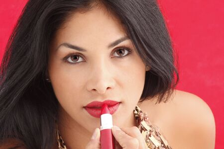 Cute brunette putting on red lipstick Stock Photo - 5141839