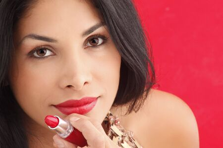 Cute brunette putting on red lipstick Stock Photo - 5036939