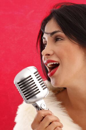 Cute brunette singer performing with a retro microphone photo