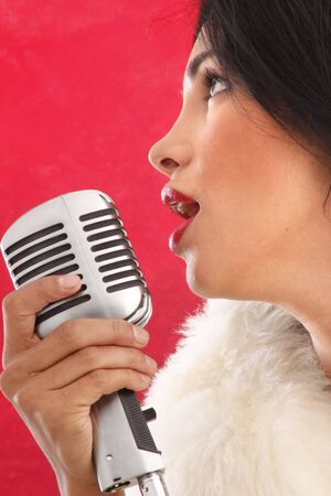 Cute brunette singer performing with a retro microphone Stock Photo - 5036967