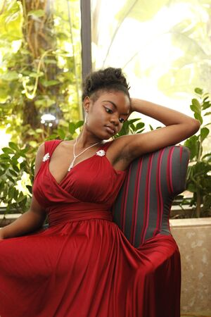 Cute african american in a burgundy gown on a matching chair