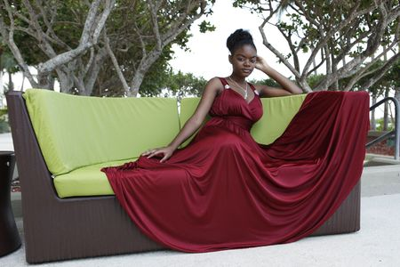 Cute african american  in a burgundy gown on a design couch photo