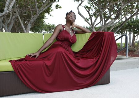 Cute african american  in a burgundy gown on a design couch