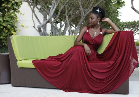 woman on couch: Cute african american  in a burgundy gown on a design couch