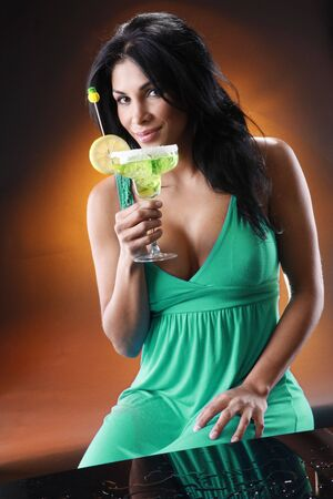 Young woman sips a Margarita. Shot to match the