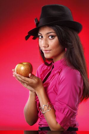 Cute teen with black hat and apple on red photo