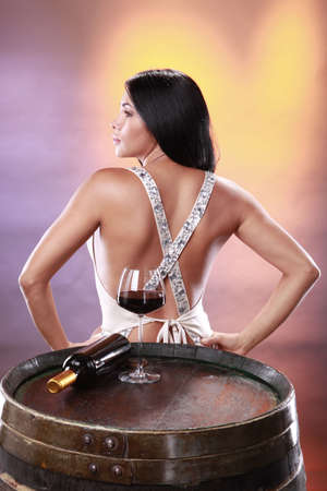 Cute brunette tasting red wine on a cellars barrel photo