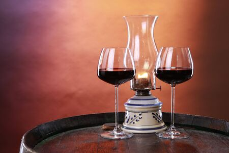 A couple of red wine glasses and an oil lantern on a barrel top Stock Photo - 5556139