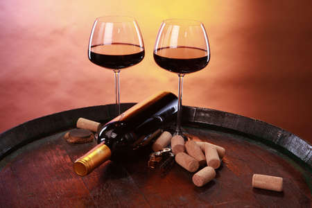 A couple of elegant red wine glasses and corks on a barrels top photo