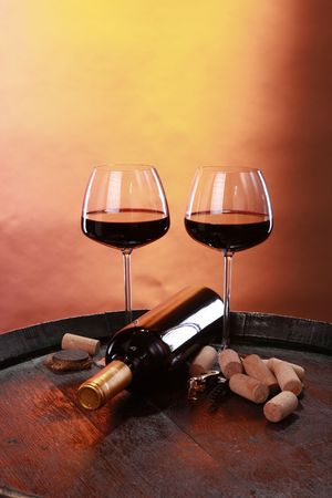 A couple of elegant red wine glasses and corks on a barrel's top Stock Photo - 5556144