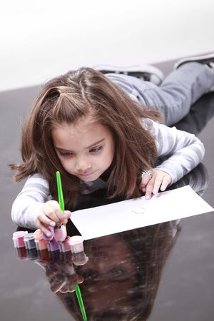 children painting: Young girl painys on the floor