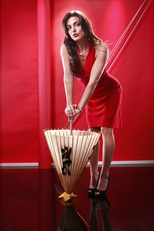 Cute brunette holding chinese umbrella on red Stock Photo - 5779820