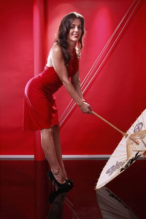 Cute brunette holding chinese umbrella on red Stock Photo - 5747836